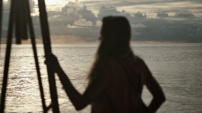 Silhouette of young woman on the sunset. Rear view. Young beautiful woman standing towards the sun on sea beach during an amazing sunset. Young woman standing on a beach and looking to a sea. - 4K stock video clip