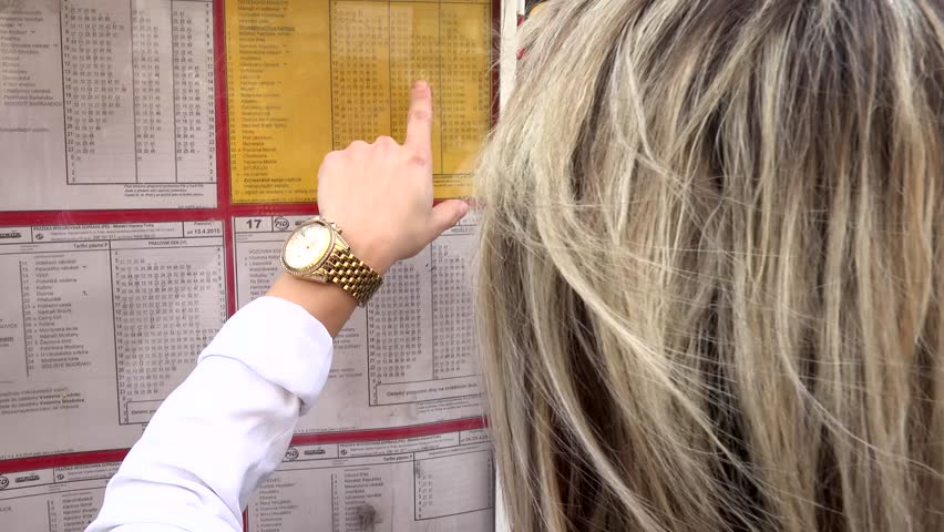young attractive blonde woman looks at the timetables (tram) and finds her transit line - shot from back