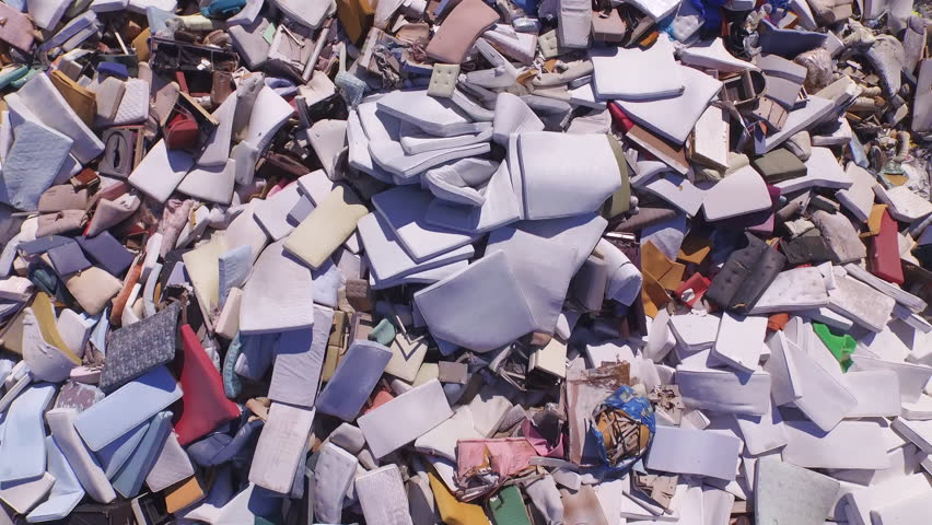 AERIAL: Big piles of old mattresses and sofas in the garbage dump