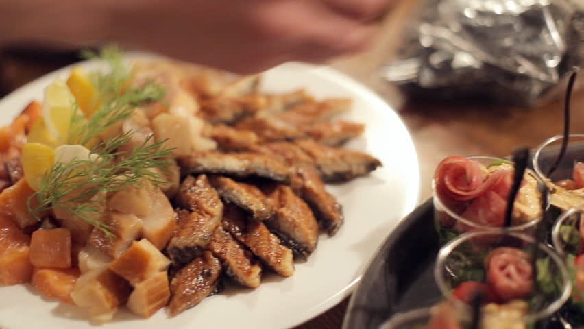 Mouth-watering dishes with fish and small portions of salad on the catering