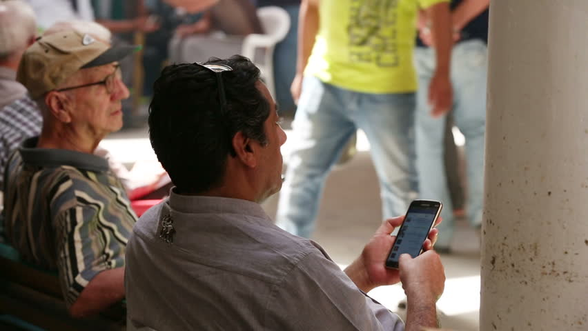 BAGHDAD, IRAQ - MAY 2015: Iraqi man uses his mobile at Mutanabbi street in Baghdad. Mutanabbi Street where writers and intellectuals meet is the historic center of Baghdad bookselling
