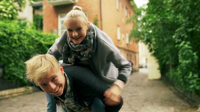 Boy wearing his girlfriend on piggyback and smiling to the camera