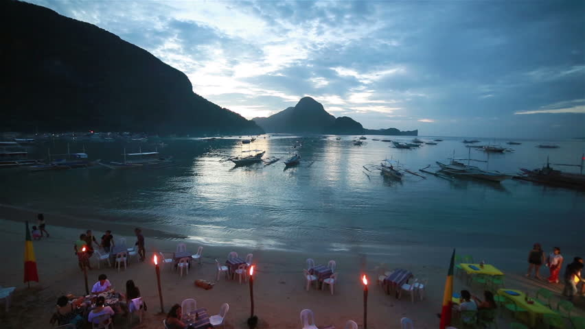 El Nido, Philippines - June 27 2015: Tourists enjoy the evening on various beach bars in El Nido by the stunning Bacuit Archipelago in Palawan in the Philippines.