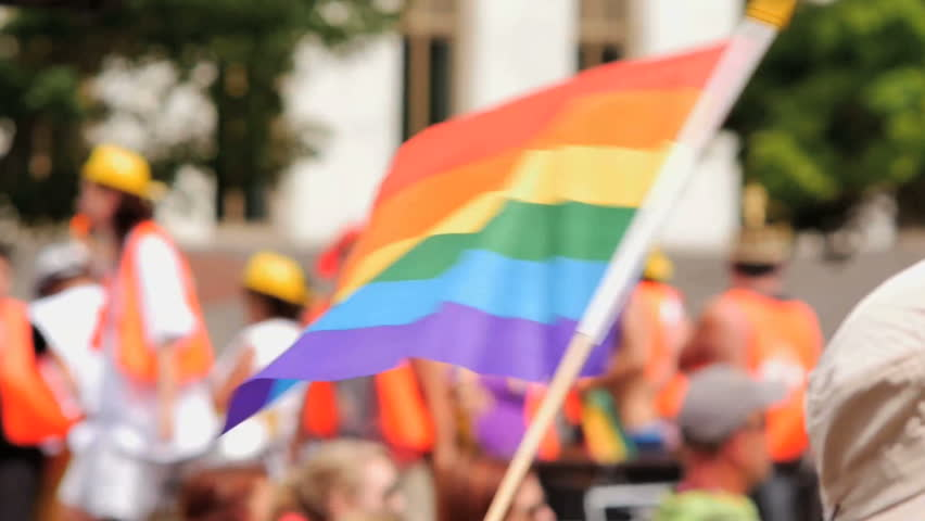 A Rainbow flag waves as a float of excited gay pride supporters pass by in the background. Slow motion 96fps.