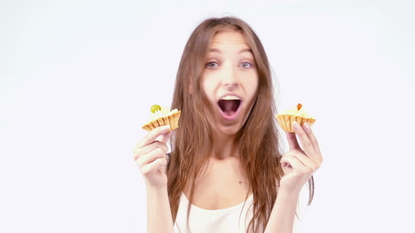 Cheerful woman eating pie, on a light background - 4K stock video clip