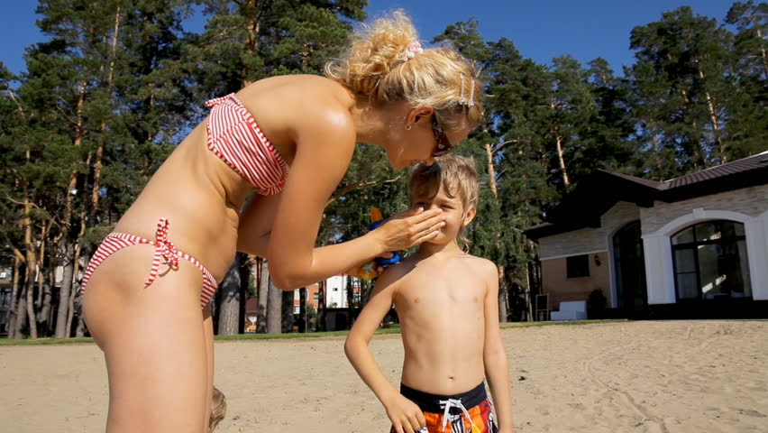 Mother and son applying sun screen lotion on the beach. Healthy sunbathing. - HD stock footage clip