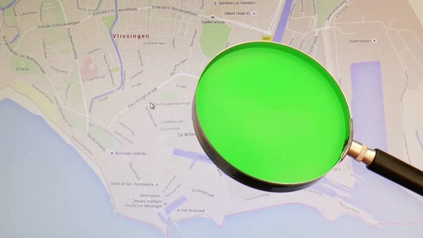 A viewpoint on a region in google map with a green screen magnifying glass. A green painted magnifying glass in front of a monitor showing a google map - HD stock footage clip