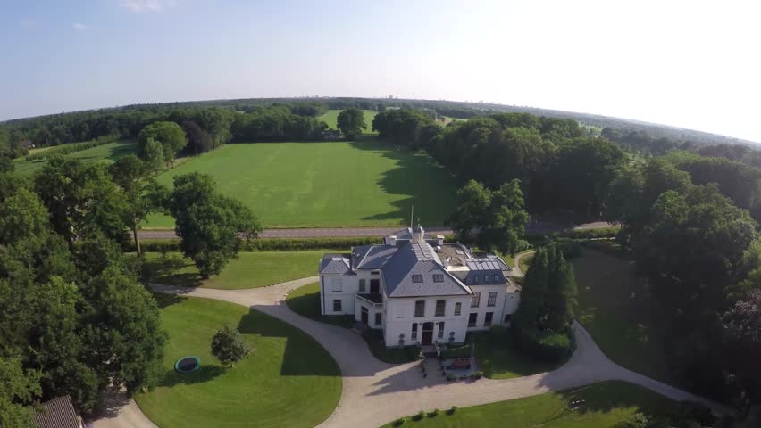 Drone aerial bird eye helicopter view of beautiful classic luxury real estate white house villa mansion and later flying over a small farm through and over trees green field and crisp blue sky 4k - 4K stock video clip