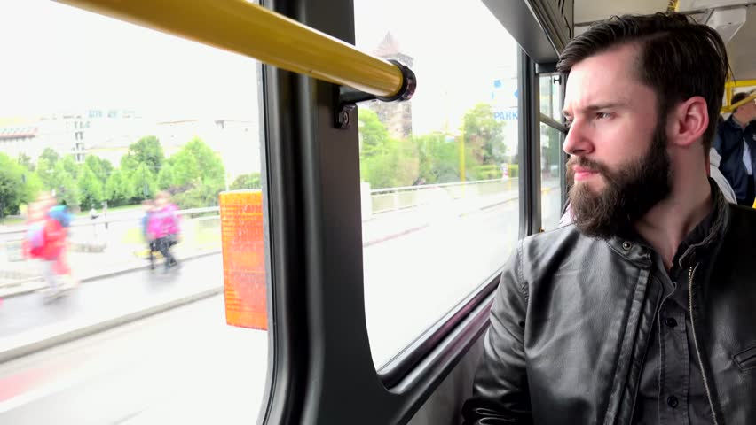 young handsome hipster man travel by tram and looks out from the window