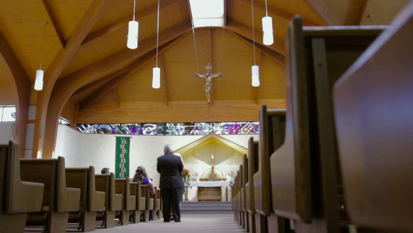 Interior of a catholic church as people walk in. - HD stock video clip