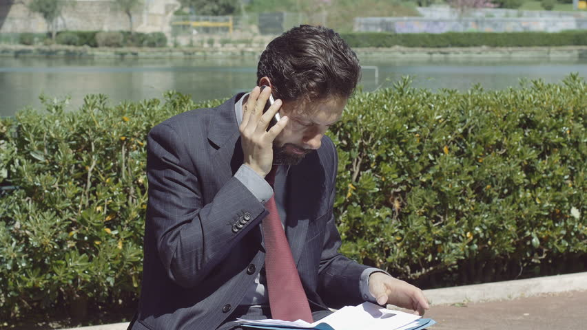 businessman working outdoor with his smartphone and documents - 4K stock video clip