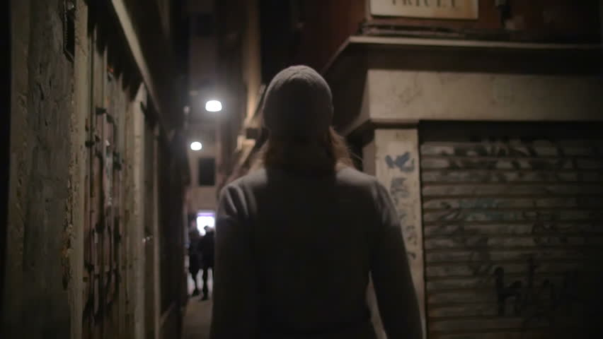 Steadicam slow motion shot of a young woman walking along the narrow street of an old town. She's lifting her head to view buildings around her.