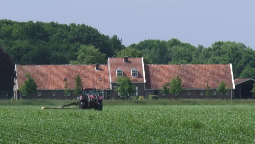 VEENHUIZEN, THE NETHERLANDS - JULY 2015: Tractor tilling field in front of traditional Veenhuizen farmhouse with with barns to either side and living accommodation in the middle - medium shot | Shutterstock HD Video #10878791