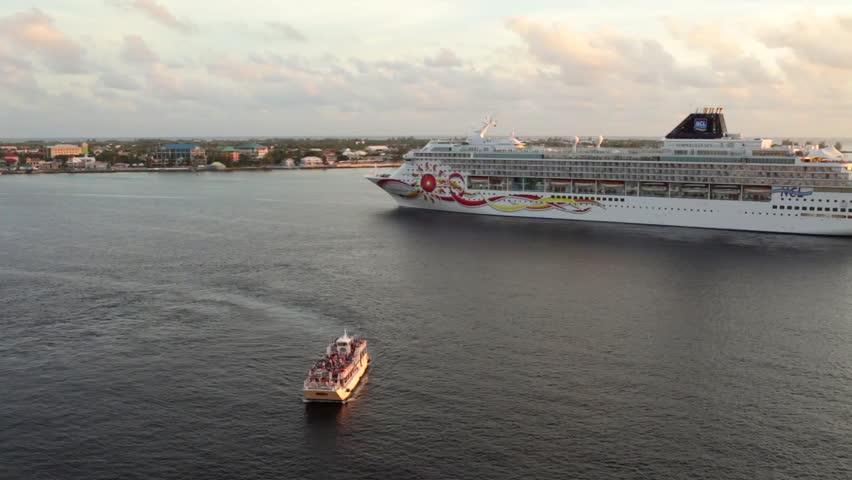 GRAND CAYMAN, CAYMAN ISLAND - 20 JULY 2012: Carib Empress tender boat sailing aside of NCL large cruise ship