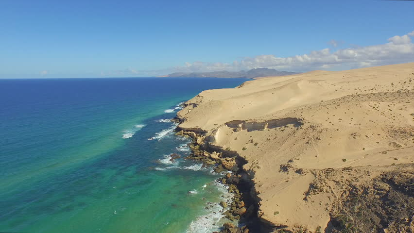 AERIAL: Flying over beautiful wild beach with desert dunes and emerald ocean | Shutterstock HD Video #10888394