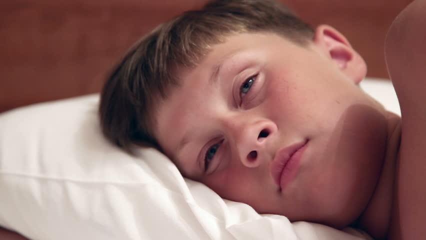 ANAPA, KRASNODAR REGION/RUSSIA - JULE 01: The boy lies in bed, asleep, closes eyes on Jule 01, 2015 in Anapa  - HD stock video clip