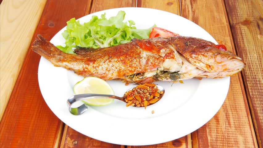 Main portion of two grilled fish served on plate with for Fish on main