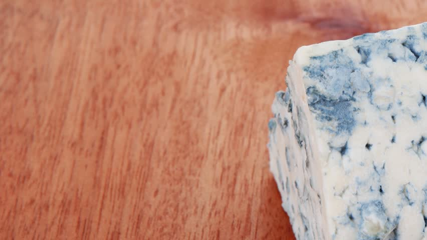bit of aged french blue roquefort or cheese on wooden table 1920x1080 intro motion slow hidef hd - HD stock footage clip