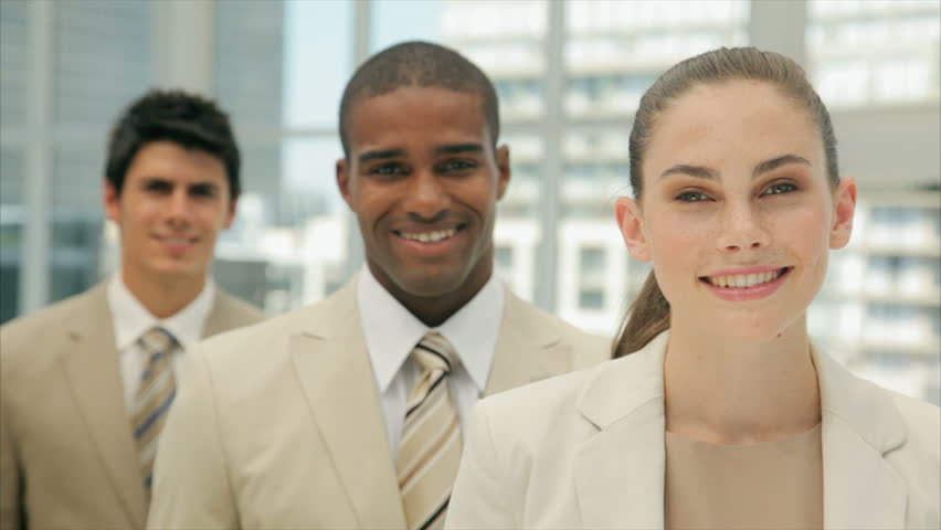 Young confident businesswoman smiling with colleagues. Young business people are in formals. Multi-ethnic female and male professionals are in brightly lit office.