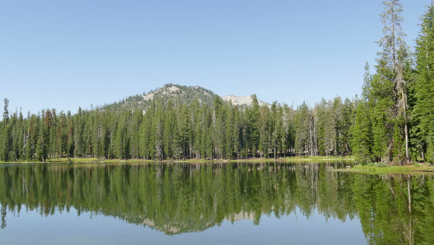 Pine forest and mountain peak reflection in a lake at Lassen Volcanic National Park, in Northern California, USA.  Filmed in 4k High Definition.