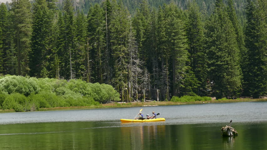 Lassen Volcanic National Park, California, USA, Summer 2015: A Family (Father, Mother, and Child) paddling a kayak on Manzanita Lake.