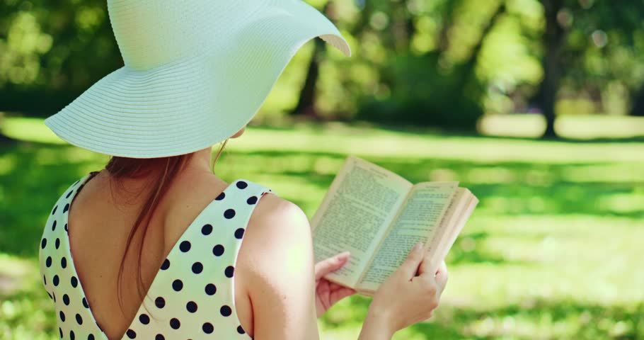 Woman reading a book in the park outdoors. Slow motion. Beautiful romantic lady in white hat sitting on the green grass lawn and looking through the novel pages and daydreaming. 4K, DCi.