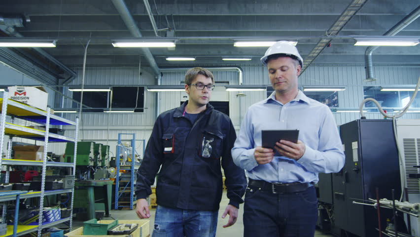 Engineer in Hard Hat and Factory Worker are Walking through Production Facility. Shot on RED Cinema Camera in 4K (UHD).