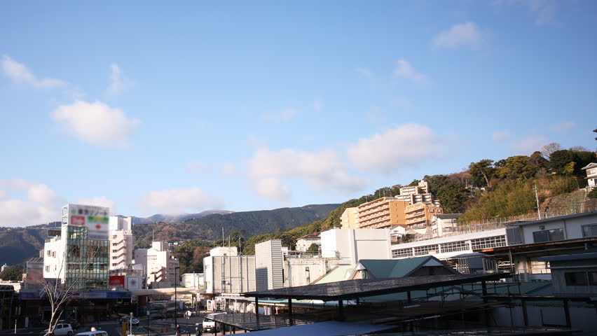 Time lapse footage with pan left motion of cloudscape over Atami Station in Shizuoka, Japan