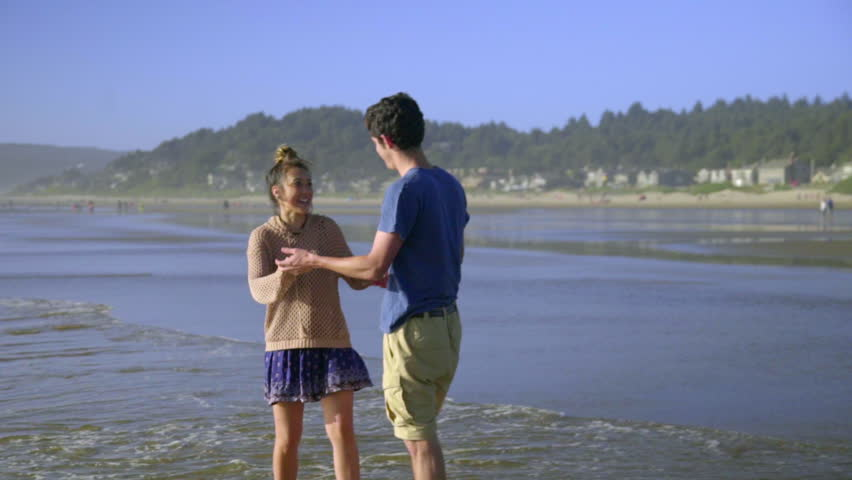 Attractive teenage boy and girl dance together in the ocean surf  - HD stock video clip