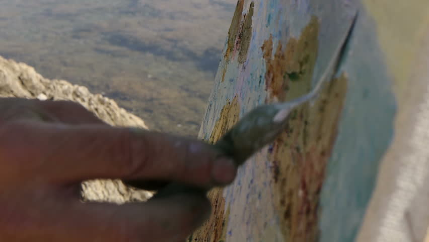 /NOT RELEVANT - JUL 18 2015: A middle-aged artist im shirt and hat make a picture of the sea standing on the stone beach of the shore, sunny summer day, close-up. - HD stock footage clip