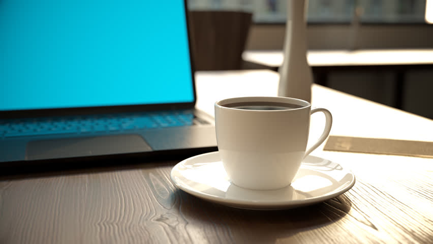 laptop and cup of hot coffee on table stock footage video