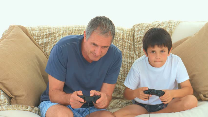 A child playing video games with his grandfather on the sofa - HD stock footage clip