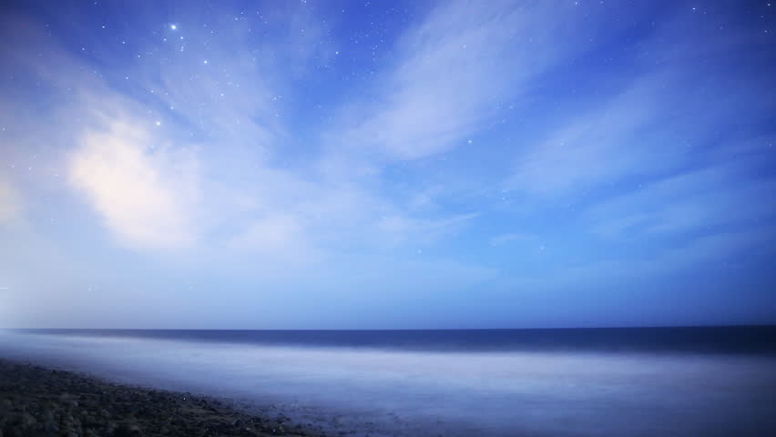 Astrophotography Time Lapse footage with zoom in motion of Milky Way galaxy rising over Night Seascape with scattered clouds in Malibu Beach, California - 4K stock footage clip