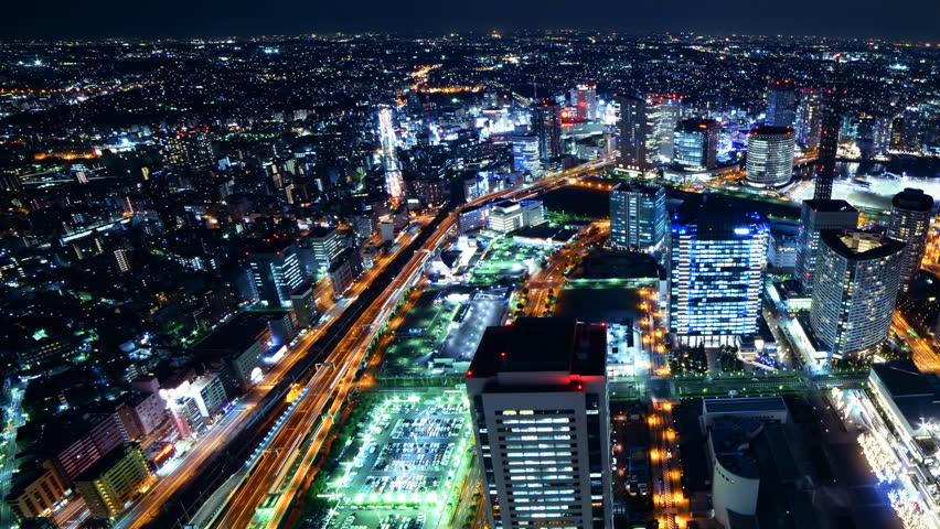 Time lapse footage with pan right motion of metropolitan cityscape at night shot from Yokohama Landmark Tower in Japan