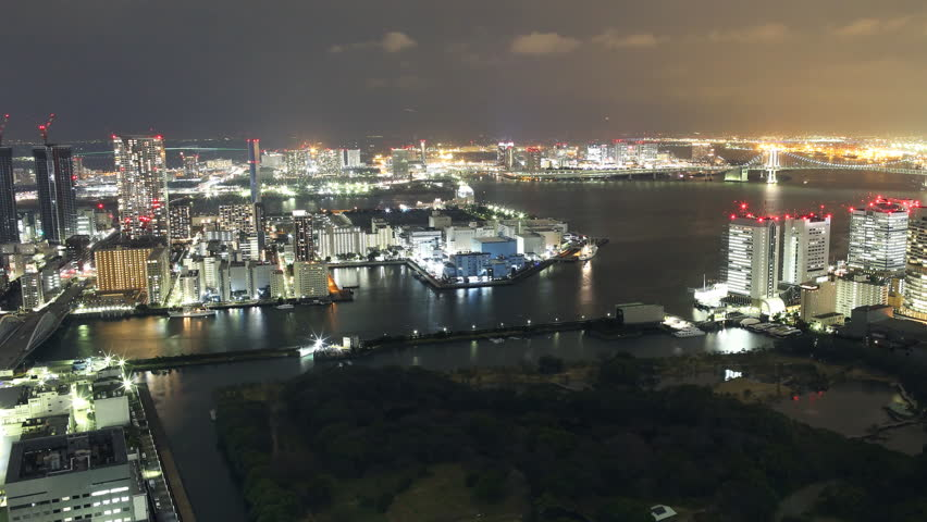 Time lapse footage with zoom out motion of metropolitan waterfront district at night in Tokyo, Japan