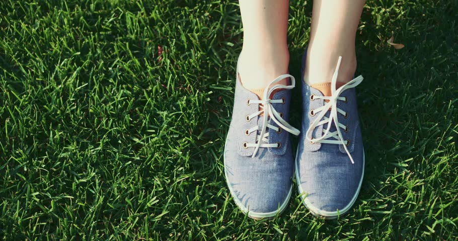 Female feet in sneakers gumshoes moving and posing on a sunlit green grass, close up. Woman's feet in blue jeans color sports shoes. Slow motion, 120fps. 4K, DCi. #11142572