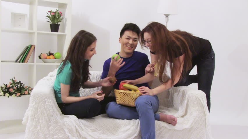 Three young people have a party and eating different fruits - HD stock video clip