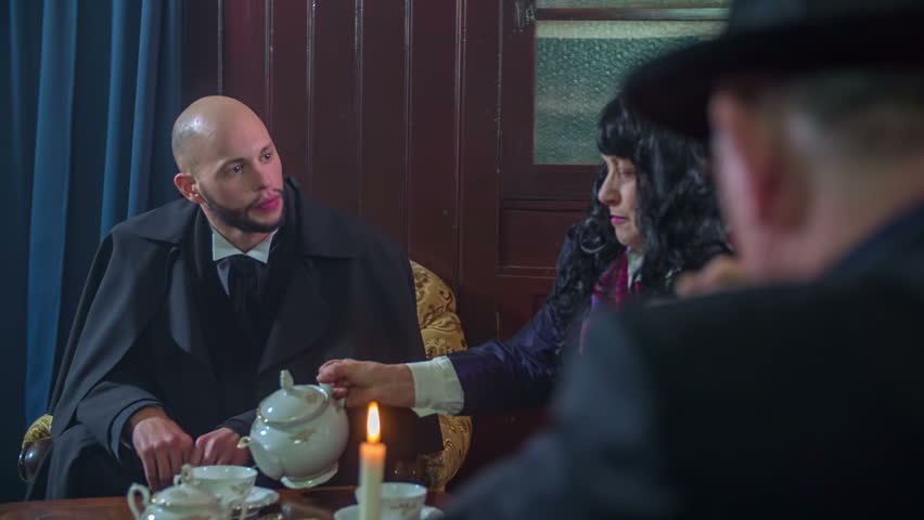 Man seating at the table wit a host and his lady and starting talking about his life journey, footage is taken in slow motion.