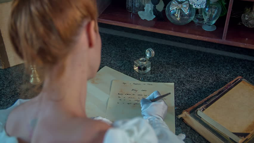 Beautiful lady seating behind the table and writing a poem in a form of letter, close up footage in slow motion.