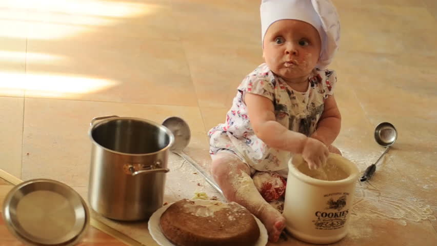A little cute ten-months-baby-girl with cooking hoods on her head is sitting on the kitchen floor, she is heavily soiled with wheat flour - she's playing cook #11174801