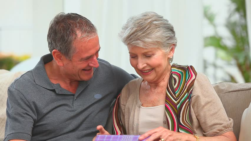 Middle aged couple with a gift looking at the camera in the living room - HD stock footage clip