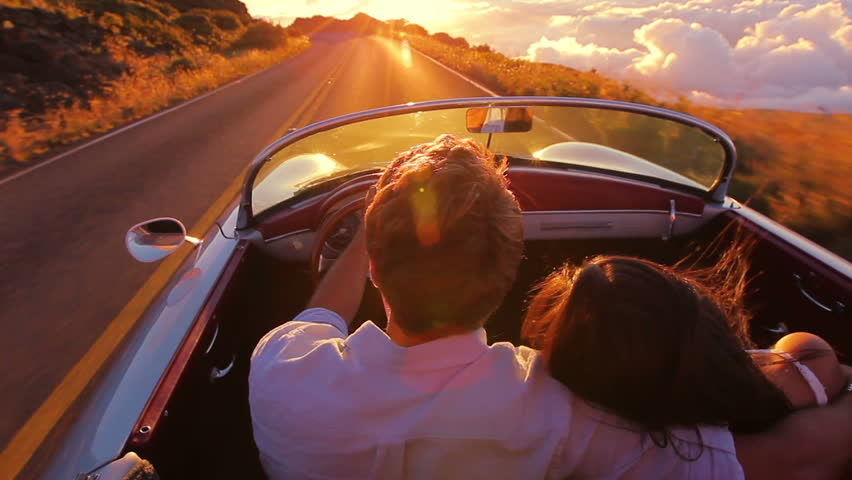 Happy Couple Driving on Country Road into the Sunset in Classic Vintage Sports Car. Steadicam Shot with Flare. Romantic Freedom Love Concept.