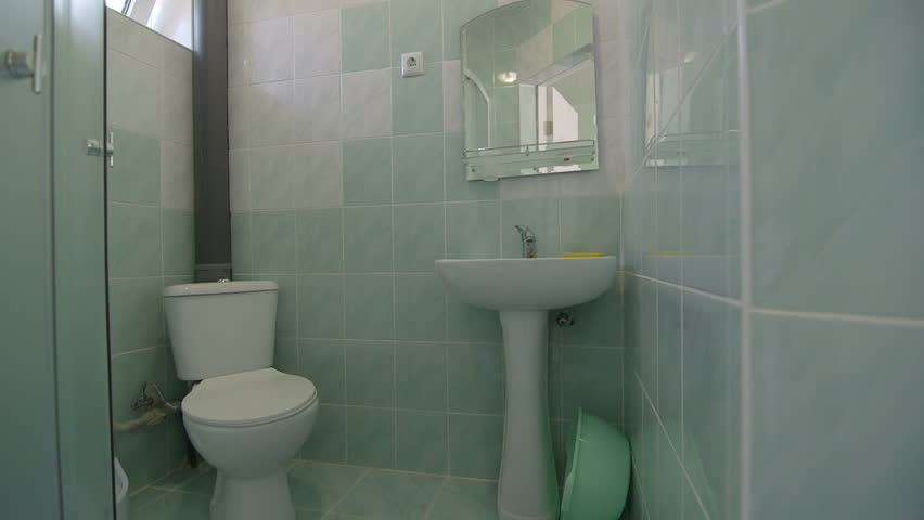 Bathroom with toilet sink and shower in cheap budget hotel room pan shot