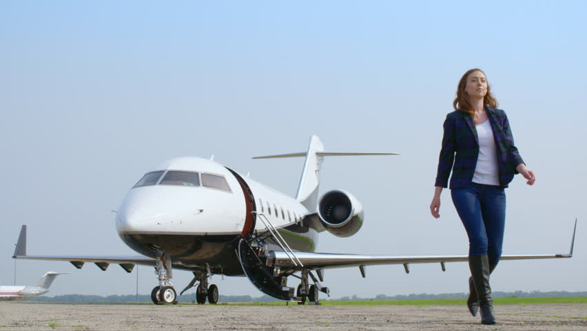 Attractive brunette in a blue jacket and jeans walking away from an executive jet at an airfield.  Wide view, originally recorded in slow motion 4K at 60fps.