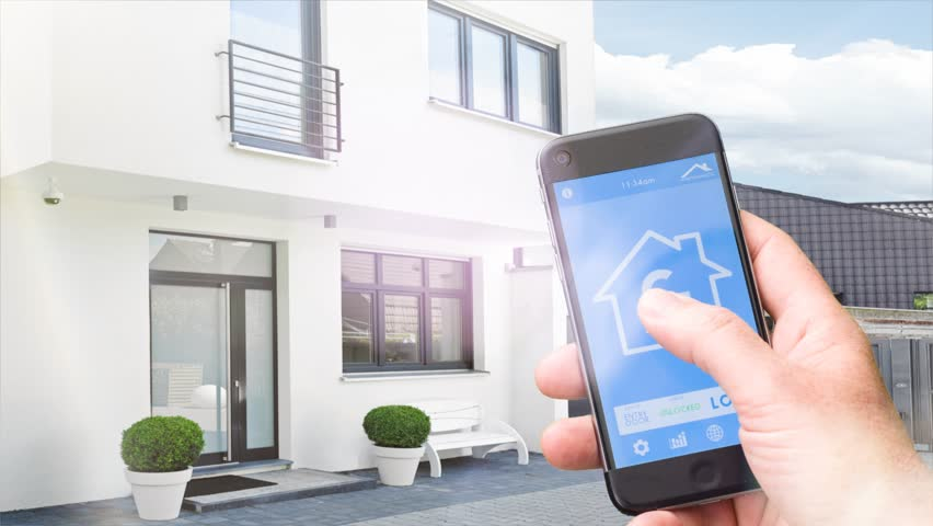 smart home - smart house, smart home automation, device with app icons. Man uses his smart phone with smarthome security app to lock the door of his house. (Shot on RED)