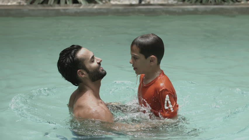 Man throwing his son while enjoying in swimming pool - 4K stock footage clip
