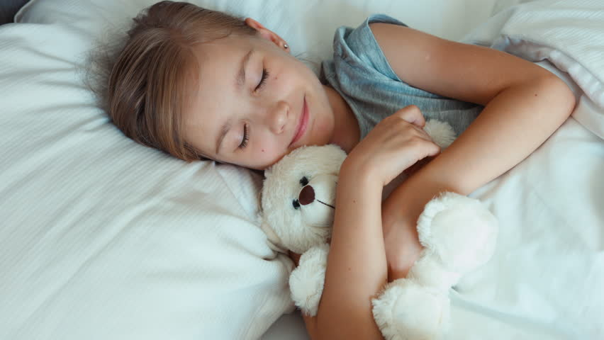 Portrait girl child hugging teddy bear in a bed. Top view