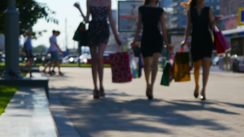 Three friends, young girls walking on street of big city with bunch of shopping bags, defocused. Consumerism concept. - 4K stock footage clip