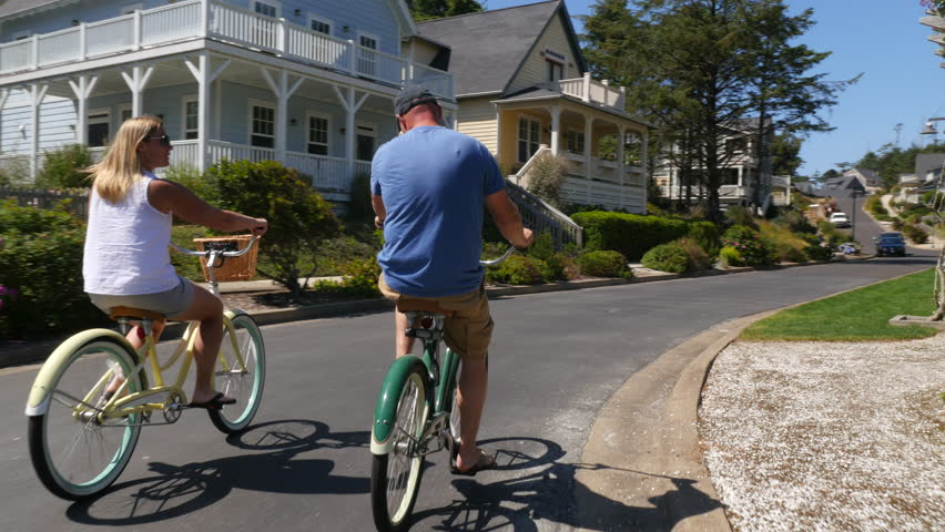 Couple riding bicycles together in coastal vacation community