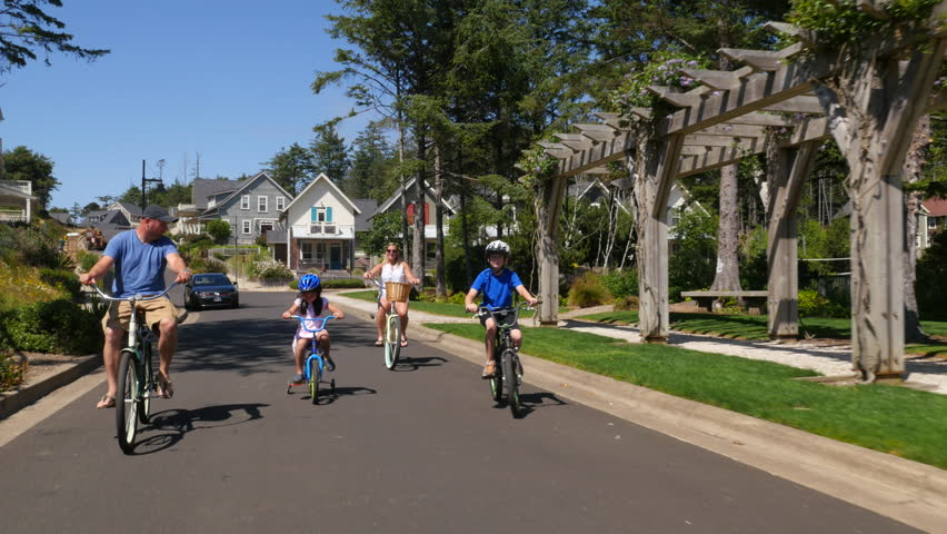 Family riding bicycles together in coastal vacation community